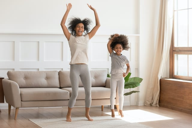 African mom with kid girl jumping dancing in living room